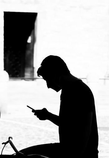 Side view of silhouette man using smart phone
