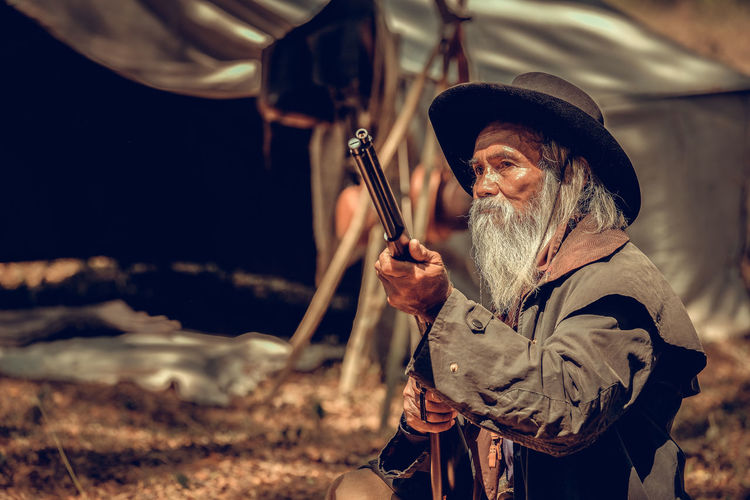 Bearded senior man aiming from gun