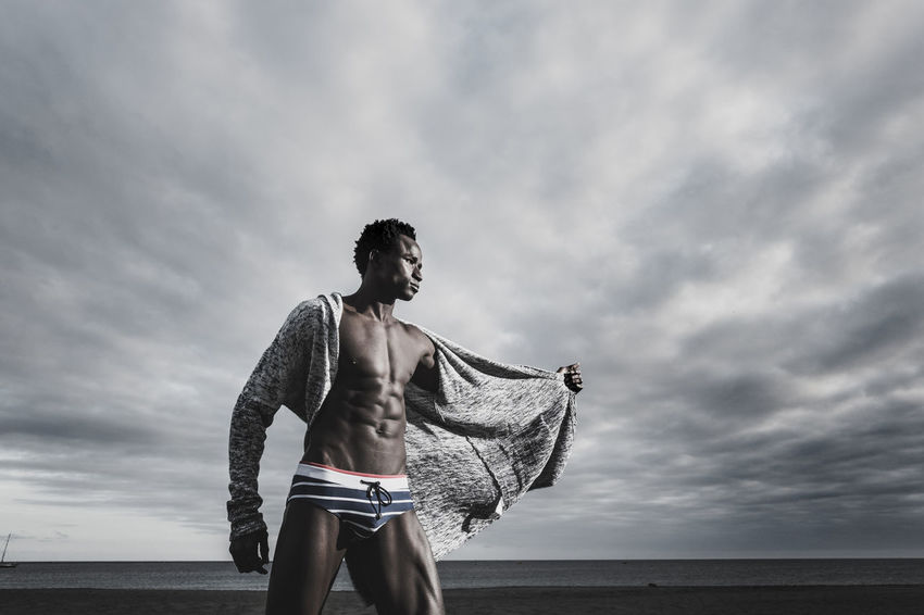 fashion and trendy concept for handsome black race afro model with swimsuit and jacket posing at the beach with ocean and blue sunset sky in background. Cold metal filter colors 25-29 Years Afternoon Casual Clothing Cloud - Sky Day Dramatic Landscape Horizon Over Water Land Leisure Activity Lifestyles Low Angle View Muscles Nature One Person Outdoors Real People Sea Sky Sports Training Standing Teenager Three Quarter Length Water Young Adult Young Men