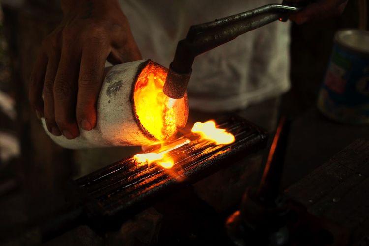 Midsection Of Manual Worker Heating Metal In Workshop