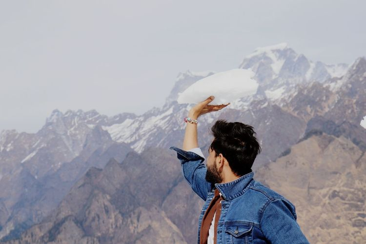 Rear view of man holding snow on mountain against sky