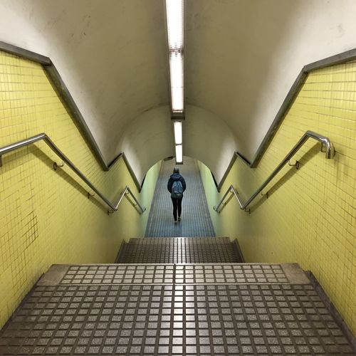 Rear View Of Woman Walking In Illuminated Subway