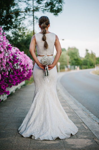 Bridal Bridal Photoshoot Bridal Bouquet Wedding Dress Wedding Day Wedding Wedding Photography Full Length Real People Rear View One Person Newlywed Bride Women Standing Plant Clothing Adult Celebration Life Events Event Flower Young Adult Fashion Outdoors Bouquet Flower Arrangement