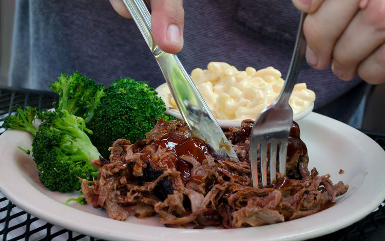 Hands use a fork and knife to eat mac and cheese, steamed broccoli and pulled barbecued brisket Broccoli Chopped Close-up Deinner Eating Utensil Food Food And Drink Fork Freshness Hand Healthy Eating Human Hand Indoors  Kitchen Utensil Mac And Cheese Meat Plate Ready-to-eat Real People Smoked Pulled Brisket Table Vegetable Veggies