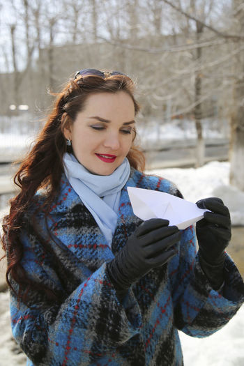 Woman holding paper boat standing outdoors during winter