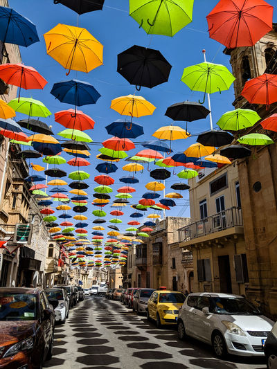 Multi colored umbrellas hanging on street in city