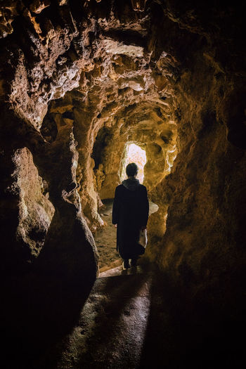 Rear view of man standing in cave
