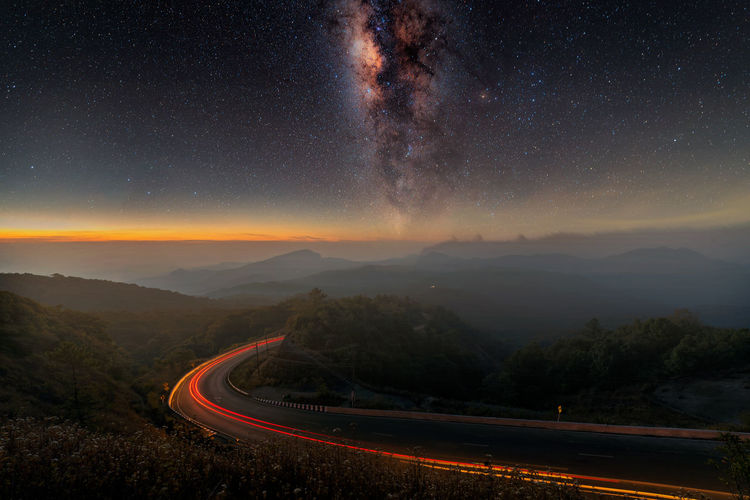 Light trails on road against starry sky at night