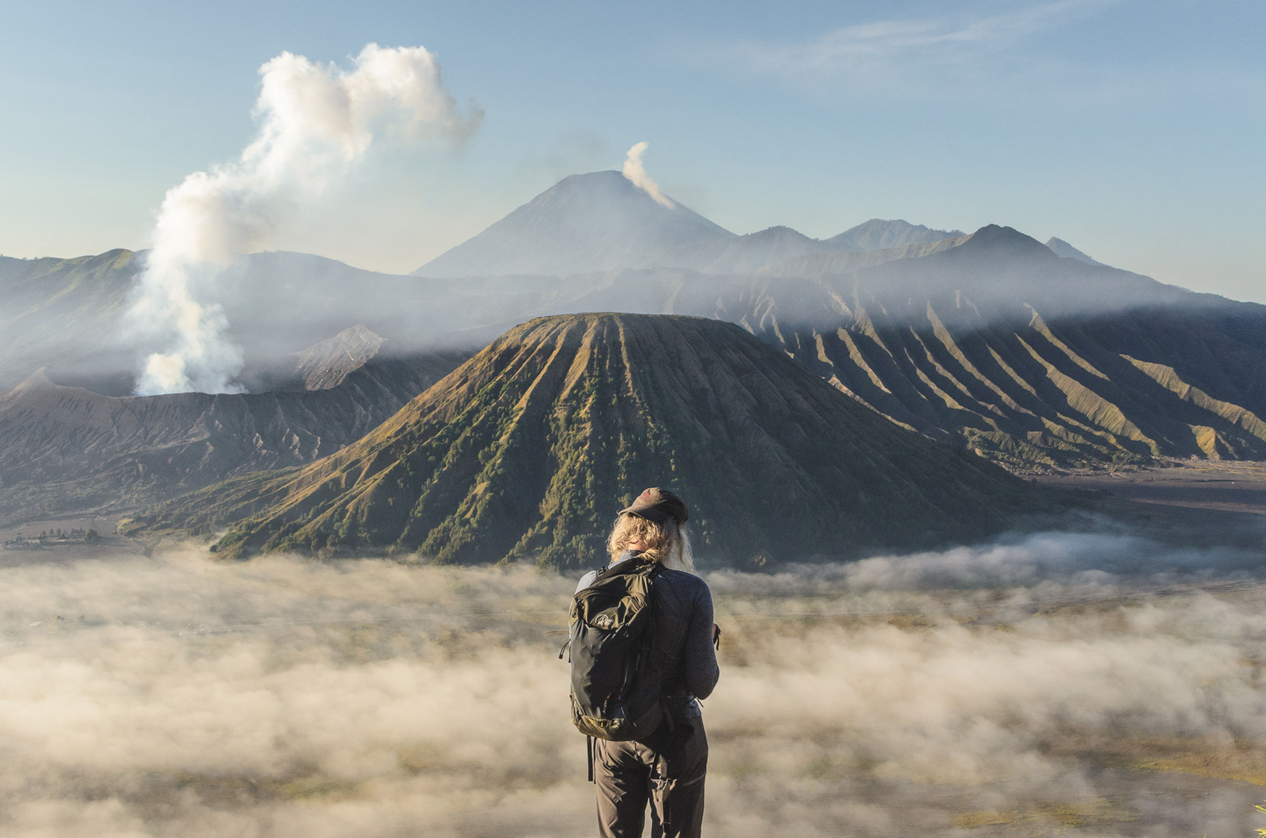mountain, scenics - nature, beauty in nature, leisure activity, one person, non-urban scene, standing, real people, tranquil scene, tranquility, lifestyles, sky, young adult, idyllic, nature, environment, volcano, smoke - physical structure, mountain range, outdoors, hairstyle