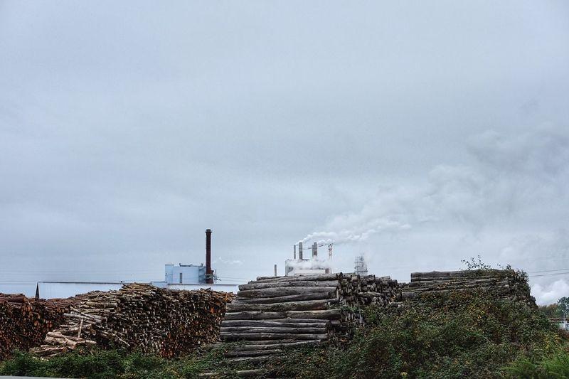 Factory emitting smoke against sky