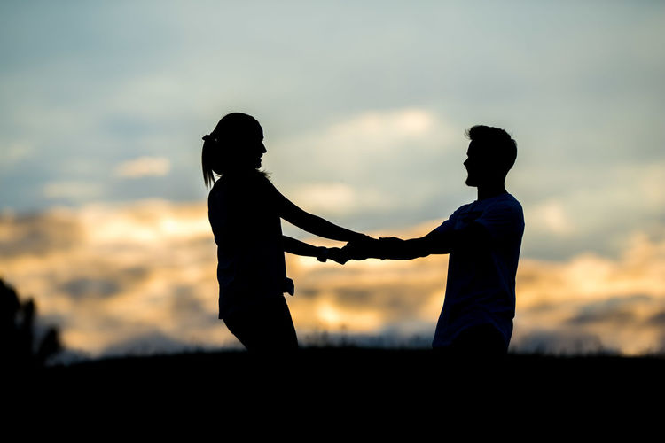 Adult Beauty In Nature Bonding Childhood Friendship Leisure Activity Lifestyles Love Men Nature Orange Color Outdoors People Real People Silhouette Sky Standing Sunset Togetherness Two People Women