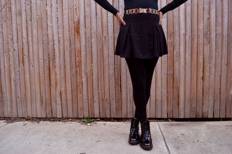 Low section of woman standing on sidewalk with legs crossed at ankle against wooden fence