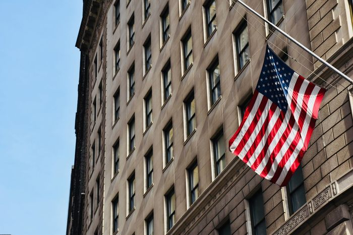 United States New York New York City Patriotism Flag Low Angle View Building Exterior Architecture Built Structure Day Window No People Outdoors Hanging Sky Stars And Stripes Close-up White Red Blue Blue Sky