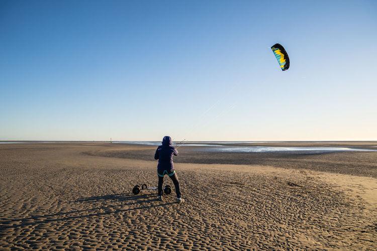 Woman kiteboarding at beach against clear sky