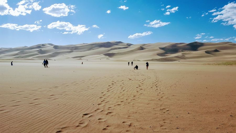 People on desert against blue sky
