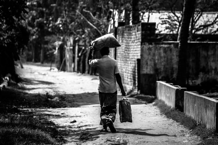 Rear view of man carrying sack while walking on road