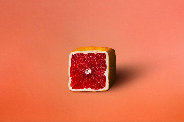 Close-up of grapefruit against orange background
