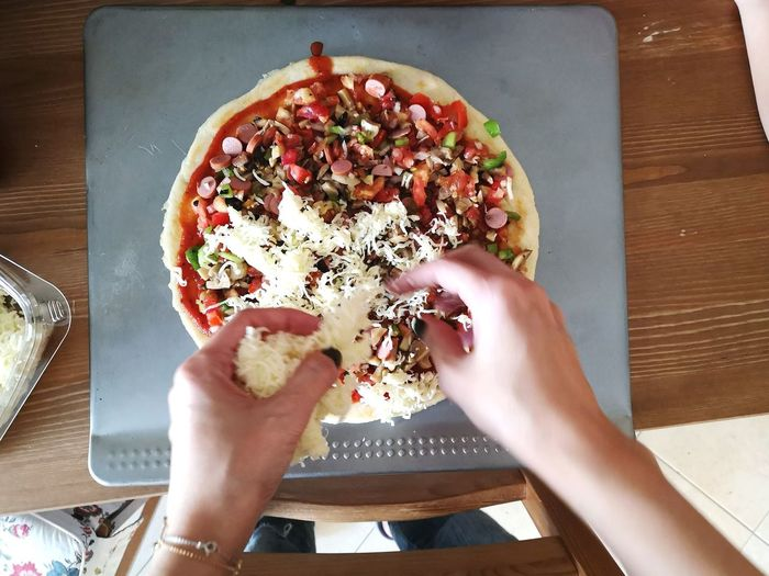 High angle view of hand holding pizza