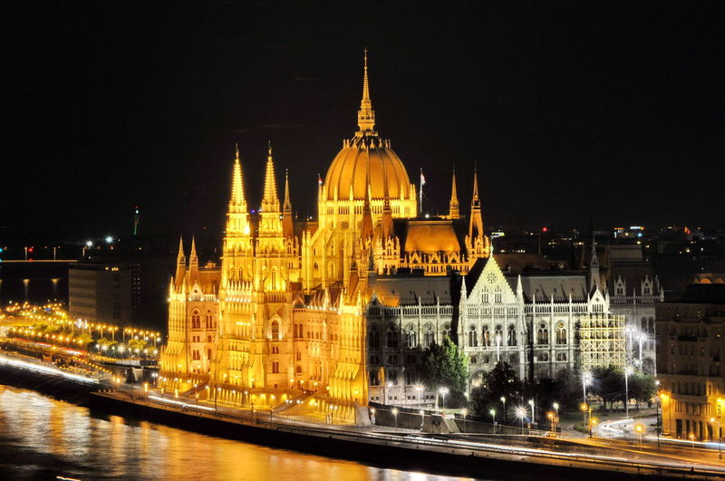 Illuminated hungarian parliament building by danube river against sky