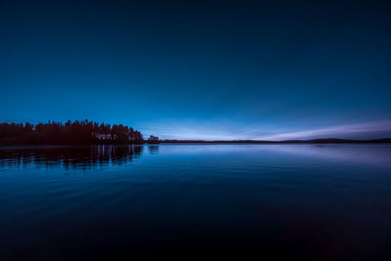 Scenic view of lake against blue sky during sunset