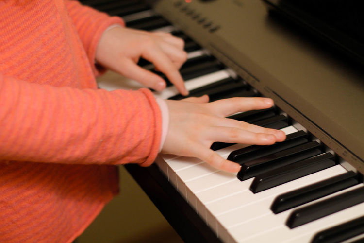 Cropped hands of boy playing piano