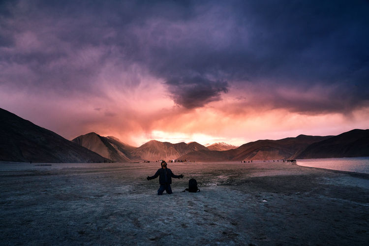 Man kneeling on land against cloudy sky at sunset