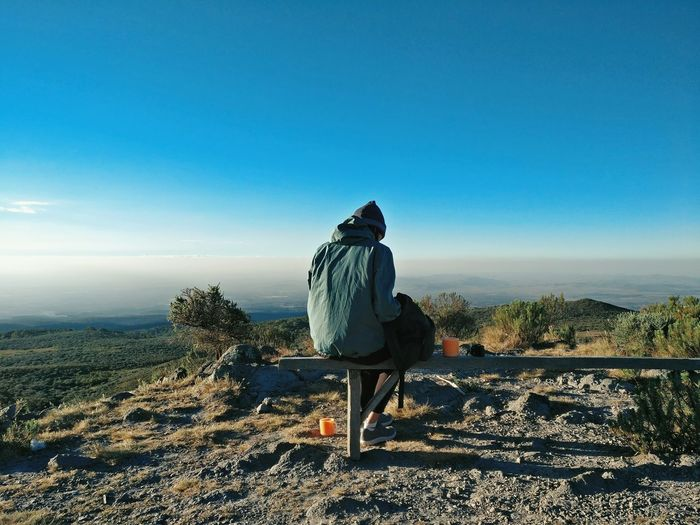 Drinking tea on a bench at the first camp of Mount Kenya. Afternoon Bench Clear Sky Climbing Day Full Length Hiking Horizon Isolated Landscape Lonely Morning Mount Kenya Mountain Mountain Range Nature One Person Outdoors Real People Rear View Scenics Self Sitting Sky Tea EyeEmNewHere