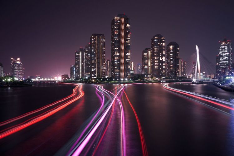 Light trails on street against illuminated city buildings at night