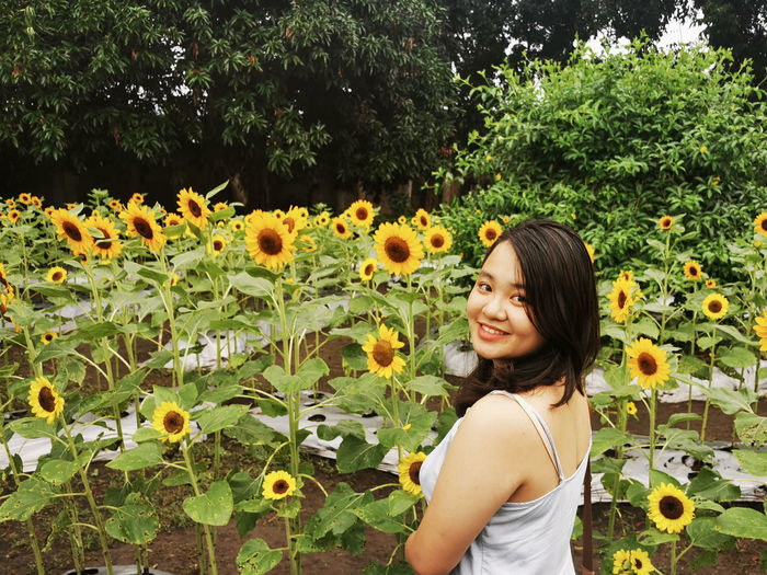 Portrait of smiling woman standing by sunflower in agricultural field