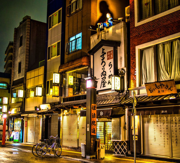 Illuminated buildings by street in city at night