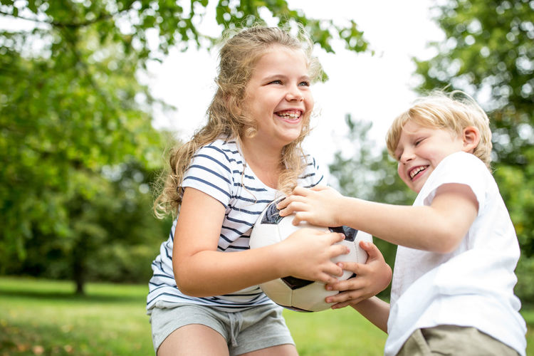 Cheerful siblings playing with soccer ball at park