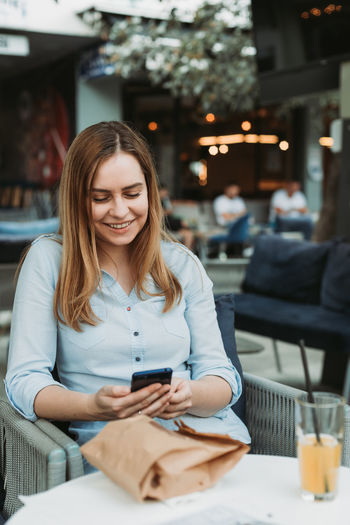 Young woman using mobile phone while sitting at cafe