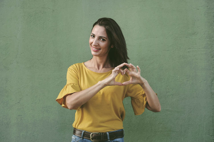 Portrait of smiling woman gesturing while standing against wall