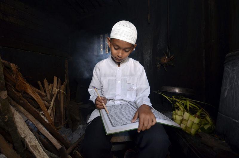 Close-up of boy reading koran in darkroom
