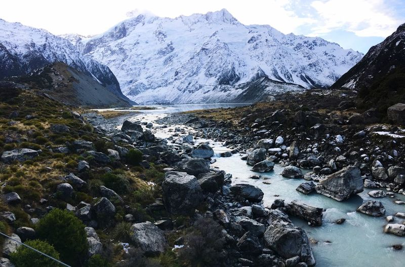 Stream by snowcapped mountains against sky