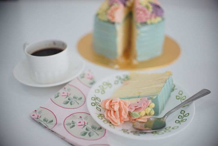 High Angle View Of Black Coffee With Cake On Table