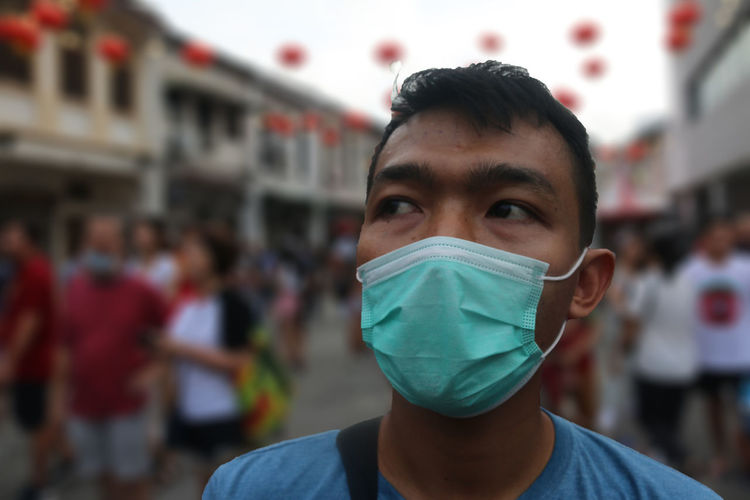 Close-up portrait of a young man with protective mask on a street