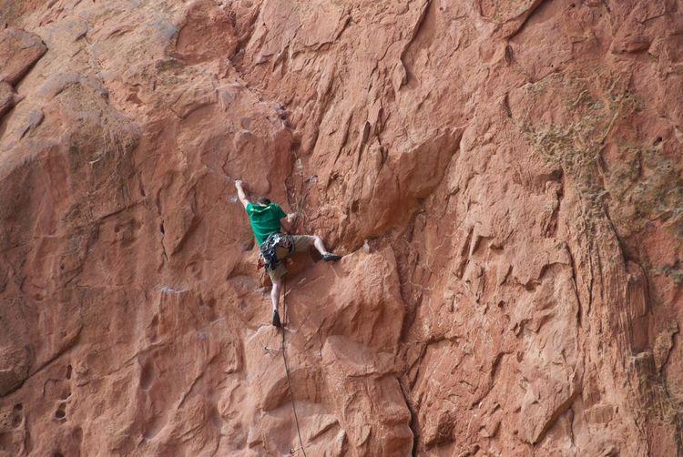 Rear view of man climbing rocky mountain