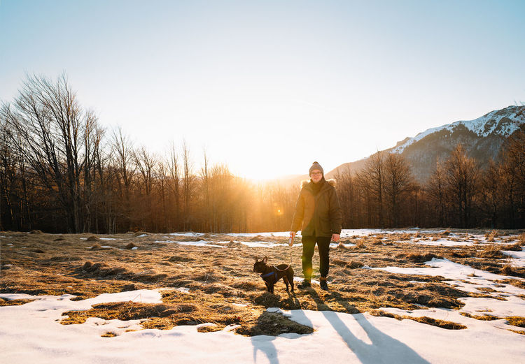 Dog owner and french bulldog on snow covered landscape against mountain and sky at sunset