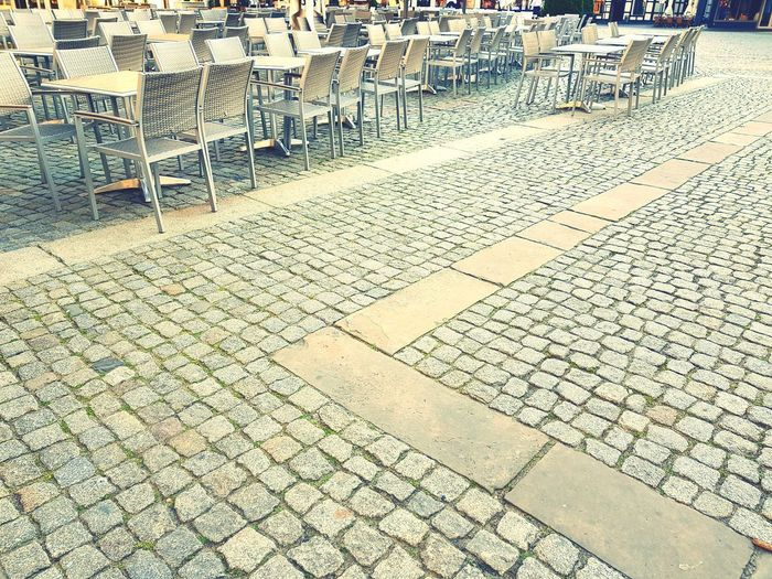 Leere Kaffeetische auf dem Marktplatz First Eyeem Photo Day Letzte Sonnenstrahlen Springtime Table Town Square Monotone Corner Man Made Space Chair Abandoned Empty Empty Chair City Light Full Frame Stone Tile Cobblestone Paved Textured  LINE Walkway