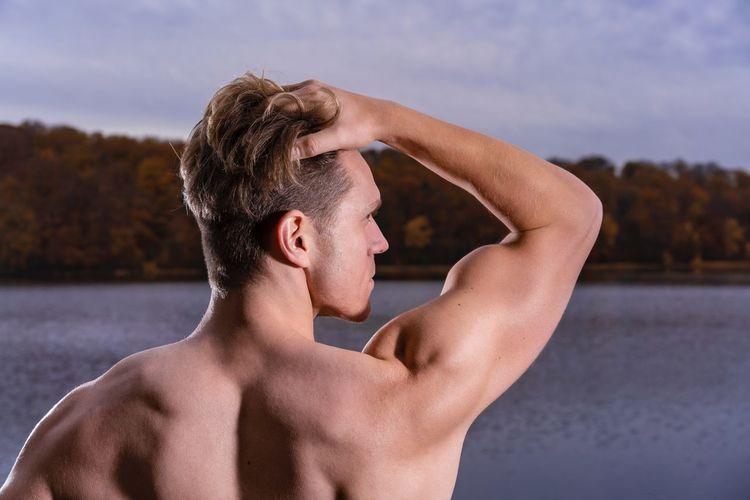 Shirtless muscular man against lake