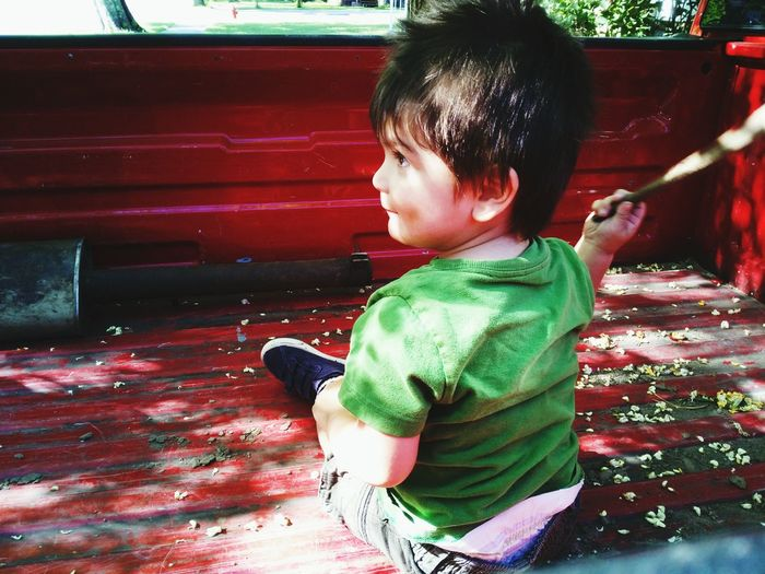 Rear View Of Boy Sitting In Pick-Up Truck
