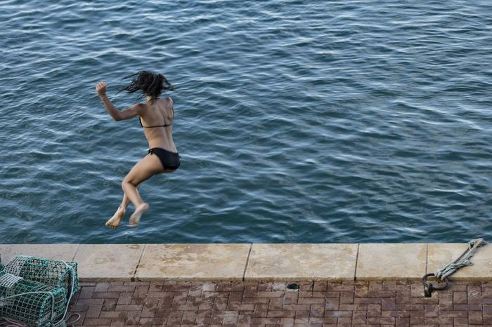 Young female person leaping into water, with back towards viewer. Some blurring creating sense of movement and joy. Day Exercise Fishing Fishing Basket Freedom Full Length High Angle View Joy Joyful Joyful Moments Jumping Leisure Activity Liberating Motion Motion Blur Nature One Person Outdoors People Quayside Real People Sea Swimming Water Young Adult #urbanana: The Urban Playground