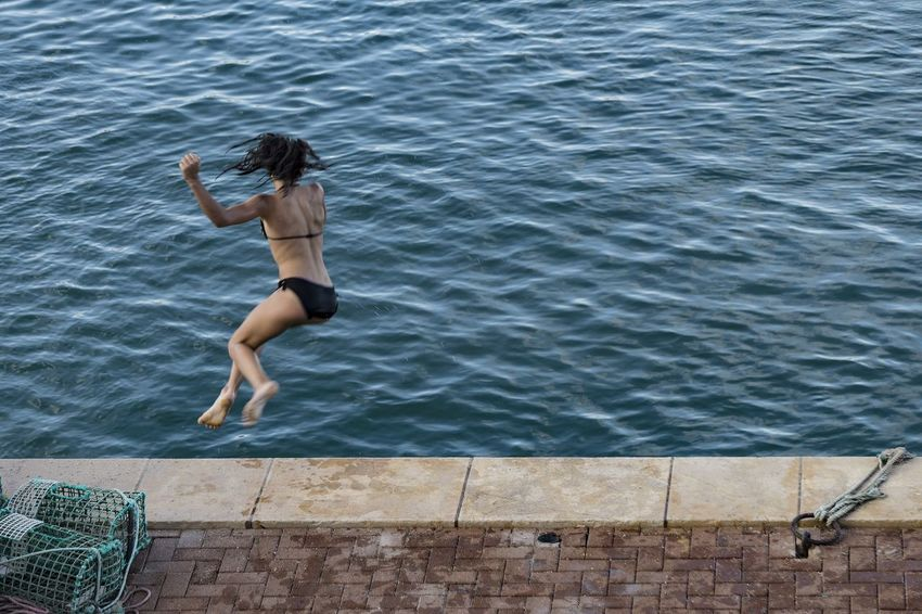 Young female person leaping into water, with back towards viewer. Some blurring creating sense of movement and joy. Day Exercise Fishing Fishing Basket Freedom Full Length High Angle View Joy Joyful Joyful Moments Jumping Leisure Activity Liberating Motion Motion Blur Nature One Person Outdoors People Quayside Real People Sea Swimming Water Young Adult