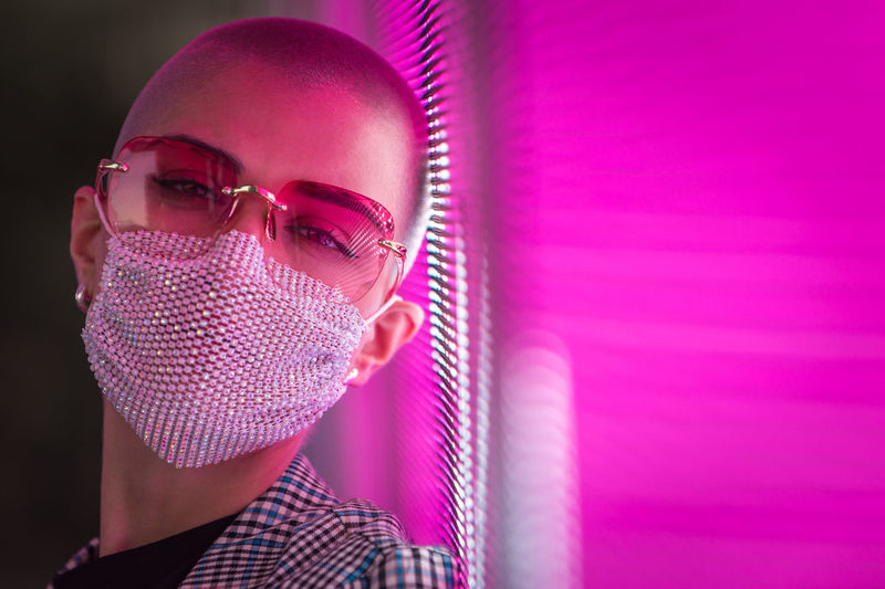Portrait of young woman with shaved head wearing mask standing against abstract backgrounds