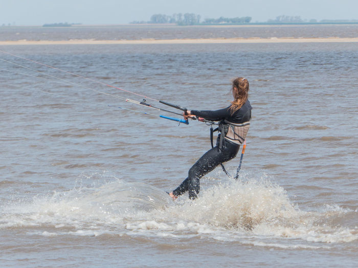 Full length of woman surfing on sea