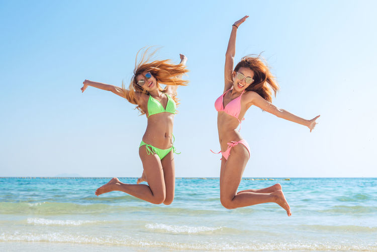 Female friends in swimwear jumping at beach against clear sky