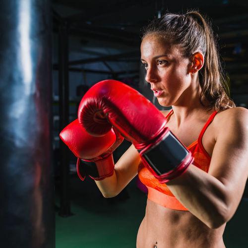 Female boxer punching bag in gym
