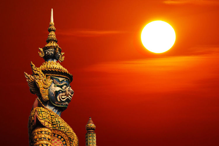 Statue of demon guardian statue in Thailand with Sun and copyspace Bangkok Statue Of Demon Guardian Statue Of Demon Guardian Statue Thailand Architecture Day Gold Colored No People Orange Color Outdoors Sky Statue Sun Sunset Yellow