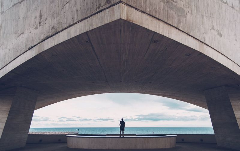 Rear View Of Man Standing Under Bridge By Sea